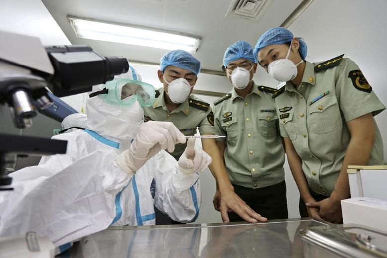 A health inspection and quarantine researcher (L) demonstrates to customs policemen the symptoms of Ebola, at a laboratory at an airport in Qingdao, Shandong province August 11, 2014. REUTERS/China Daily