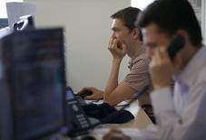 Трейдеры на торгах Московской биржи 3 июня 2014 года.Российские фондовые индексы незначительно отскочили на старте сессии и колеблются вокруг достигнутых уровней с минимальными изменениями в выходной для Лондонской биржи понедельник. REUTERS/Sergei Karpukhin