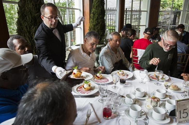 A waiter serves dessert to a table of men listening to Chinese millionaire Chen Guangbiao during a lunch he sponsored for hundreds of needy New Yorkers at Loeb Boathouse in New York's Central Park June 25, 2014. REUTERS/Lucas Jackson
