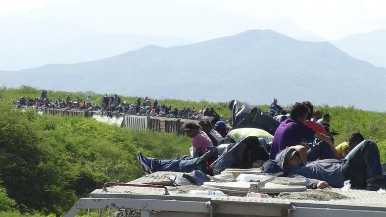 People hoping to reach the U.S. ride atop the wagon of a freight train, known as La Bestia (The Beast) in Ixtepec, in the Mexican state of Oaxaca June 18, 2014.  REUTERS/Jose de Jesus Cortes