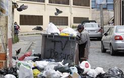 Imagen de archivo de un vagabundo revisando entre escombros durante una jornada de protestas por mejoras salariales en Valparaíso, Chile, nov 5 2013. La tasa de desempleo en Chile habría subido al 6,7 por ciento en el trimestre mayo-julio, debido a los efectos de la desaceleración de la economía y a factores estacionales por la llegada del invierno austral, mostró el miércoles un sondeo de Reuters.  REUTERS/Eliseo Fernandez