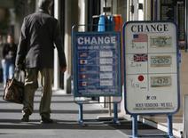 Человек проходит мимо пукта обмена валюты в Париже 24 сентября 2007 года. Курс евро снизился до годового минимума за счет войны на Украине и накануне совещания Европейского центрального банка. REUTERS/Vincent Kessler