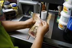Un cajero contando billetes en un supermercado en Caracas, jun 13 2014. La deuda venezolana abrió en baja el miércoles, reaccionando negativamente a un cambio del gabinete del presidente Nicolás Maduro, por el temor a que se congelen medidas de ajuste macroeconómico que aguardaba el mercado. REUTERS/Carlos Garcia Rawlins