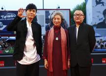 """Director Wang Xiaoshuai (R) poses with cast members Qin Hao (L) and Lu Zhong during the red carpet for the movie """"Chuangru zhe"""" (Red amnesia) at the 71st Venice Film Festival September 4 2014. REUTERS/Tony Gentile"""