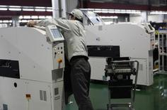 Un empleado de Panasonic Factory Solutions Co. trabaja en un robot de la firma en la prefectura de Yamanashi, Japón, abr 19 2013. La actividad empresarial global se mantuvo sólida el mes pasado, con un robusto crecimiento en los sectores de manufacturas y servicios, mostró un sondeo el jueves.  REUTERS/Reiji Murai