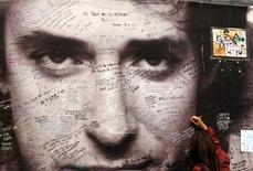 A woman writes a phrase on a giant picture of Argentine singer Gustavo Cerati fixed on a wall in front of the clinic where Cerati died today at the age of 55, in Buenos Aires September 4, 2014. REUTERS/Enrique Marcarian