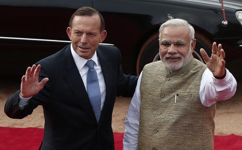 Australia's Prime Minister Tony Abbott and his Indian counterpart Narendra Modi (R) wave towards the media during Abbott's ceremonial reception at the forecourt of the Rashtrapati Bhavan in New Delhi September 5, 2014. Abbott is on a two-day visit to India. REUTERS/Adnan Abidi