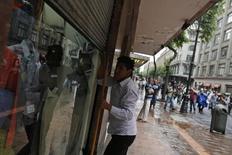 Imagen de archivo de una persona bajando la cortina de su tienda en Ciudad de México, mayo 1 2014. El índice de confianza del consumidor de México cayó en agosto por segundo mes consecutivo para ubicarse en 87.9 unidades, su nivel más bajo en un semestre, mostraron el viernes cifras oficiales ajustadas por estacionalidad. REUTERS/Tomas Bravo