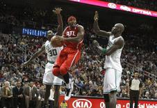 Atlanta Hawks forward Josh Smith (C), goes up for a basket between Boston Celtics forward Brandon Bass (L), and center Kevin Garnett (R), in the second half of their NBA basketball game in Atlanta, Georgia  January 5, 2013.   REUTERS/Tami Chappell