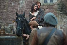 Claire Randall played by Caitriona Balfe rides a horse with Jamie Fraser played by Sam Heughan in a scene from Outlander. REUTERS/Starz