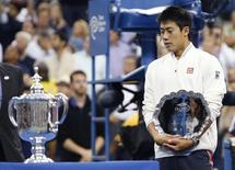 Kei Nishikori of Japan holds his runner up trophy as he looks at the winner's trophy after being defeated in the men's singles final match by Marin Cilic of Croatia at the 2014 U.S. Open tennis tournament in New York, September 8, 2014.          REUTERS/Mike Segar