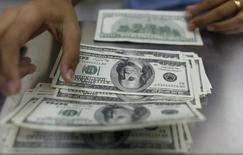 Работница обменного пункта в Янгоне считает долларовые купюры 23 мая 2013 года. Курс доллара к корзине основных валют поднялся до 14-месячного максимума, после того как отчет одного из Федеральных резервных банков США заставил инвесторов переосмыслить перспективу повышения процентных ставок ФРС. REUTERS/Soe Zeya Tun