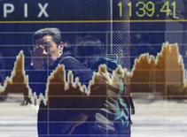 Мужчина проходит мимо табло с котировками TOPIX в Токио 14 апреля 2014 года. Фондовый рынок Японии вырос во вторник, китайский рынок не изменился, а биржи Южной Кореи и Гонконга были закрыты по случаю государственного праздника. REUTERS/Issei Kato