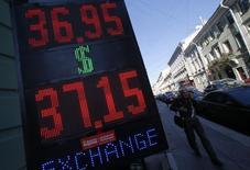 Мужчина проходит мимо вывески пункта обмена валюты в Санкт-Петербурге 9 сентября 2014 года. Рубль провел торги вторника в узких диапазонах на фоне отсрочки новых санкций Евросоюза, показывая большую часть дня положительную динамику против евро за счет падения единой валюты на форексе, но умеренную слабость - в паре с долларом из-за по-прежнему высокой геополитической неопределенности. REUTERS/Alexander Demianchuk