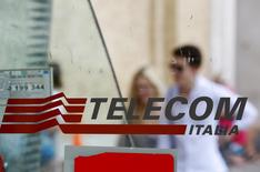 Personas pasan atrás del logo de Telecom Italia en Roma. Imagen de archivo, 28 agosto, 2014. Las acciones de Telecom Italia subían más de un 3 por ciento en las primeras operaciones del martes después de que la mexicana América Móvil dijo que sostendrá discusiones con Oi SA sobre si se suma a su oferta para comprar a la unidad brasileña del grupo italiano de telecomunicaciones. REUTERS/Max Rossi