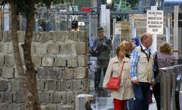 Visitors watch a replica of the Berlin Wall at an exhibition about the fall of the Wall in 1989 in a shopping center at Potdamer Platz square in Berlin September 4, 2014. REUTERS/Fabrizio Bensch