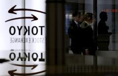 Люди проходят мимо логотипа Токийской фондовой биржи в её здании в Токио 30 января 2014 года. Азиатские фондовые рынки, кроме Японии, снизились в четверг из-за экономической статистики Китая и местных новостей. REUTERS/Toru Hanai