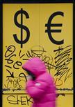 """Прохожая у обменного пункта в Москве 3 марта 2014 года. Рубль завершает вторую неделю сентября на абсолютных минимумах после запуска новых санкций ЕС и США против России и заседания совета директоров ЦБР, итоги которого участники рынка сочли """"голубиными"""", на фоне спроса на валюту США, внешнего и локального, а также низких нефтяных цен. REUTERS/Maxim Shemetov"""