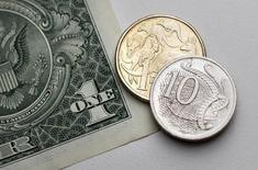 Валюты США и Австралии в Сиднее 27 июля 2011 года. Австралийский доллар подешевел до полугодового минимума из-за замедления роста китайской экономики, а другие основные валюты малоподвижны накануне совещания ФРС. REUTERS/Tim Wimborne