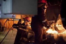 Рабочие на заводе ArcelorMittal в Темиртау 13 июня 2012 года. Крупнейшая экономика Центральной Азии, Казахстан, ждет снижения темпов роста промышленного производства в 2015 году, но обещает восстановить их в 2016 году вместе с ростом добычи нефти и стартом гигантского месторождения Кашаган. REUTERS/Valery Kaliyev
