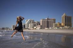 """Newly-crowned Miss America 2015 Kira Kazantsev leaps into the air while posing for photographs during her '""""Toe Dip"""" along the beachfront of Boardwalk Hall the morning after she won the 2015 Miss America Competition in Atlantic City, New Jersey September 15, 2014.   REUTERS/Adrees Latif"""