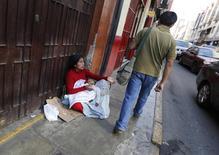 Una mujer pidiendo dinero con un menor en brazos en una calle en Lima, ago 29 2014. La tasa de desempleo en la capital de Perú subió 0,3 puntos porcentuales a un 5,9 por ciento en el trimestre móvil de junio a agosto frente al mismo período del año pasado, dijo el lunes el Instituto Nacional de Estadística e Informática. REUTERS/Mariana Bazo