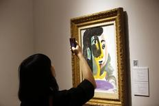 """Mulher tira foto da obra """"Tete de femme"""" antes de um leilão da Christie's, em Xangai, na China. 24/05/2014.  REUTERS/Aly Song"""