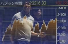 Personas son reflejadas en una pantalla electrónica que muestra el índice Hang Seng en Tokio. Imagen de archivo, 24 julio, 2014. Las bolsas de Asia avanzaban el miércoles después de Wall Street rebotó en la sesión anterior por la especulación de que la Reserva Federal de Estados Unidos no alterará su compromiso sobre las tasas de interés cuando una reunión de dos días concluya más tarde en la sesión. REUTERS/Issei Kato