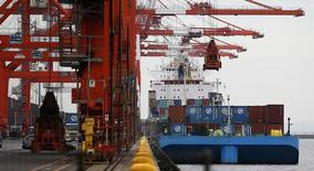 Контейнеровоз в порту Токио 18 сентября 2014 года. Правительство Японии снизило общую оценку экономики впервые за пять месяцев, так как частное потребление не может восстановиться после спада, вызванного апрельским повышением налога с продаж. REUTERS/Toru Hanai