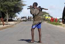 Somali government soldiers walk near the scene of a suicide car bomb explosion targeting peacekeeping troops in a convoy outside the capital Mogadishu September 8, 2014. REUTERS/Feisal Omar
