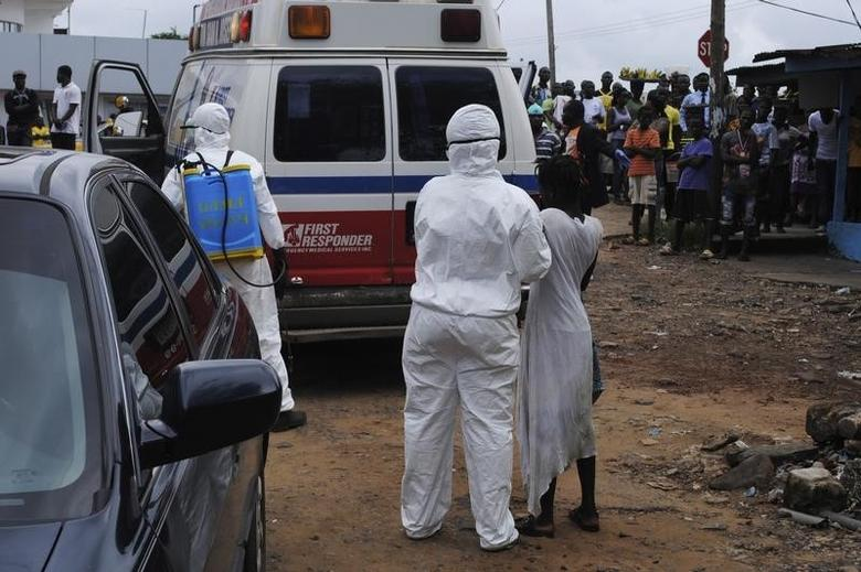 Health workers bring a woman suspected of having contracted Ebola virus to an ambulance in front of a crowd in Monrovia, Liberia, September 15, 2014. REUTERS/James Giahyue