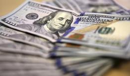 Фотография долларовых купюр в Йоханнесбурге 13 августа 2014 года. Основные валюты немного восстановились к доллару в понедельник после того, как долларовый индекс отметил десятую неделю роста подряд. REUTERS/Siphiwe Sibeko