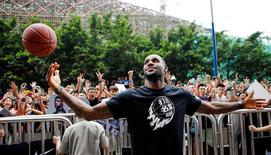 NBA basketball player LeBron James of Cleveland Cavaliers plays with a basketball during a promotional event at a store in Guangzhou, Guangdong province, July 22, 2014. REUTERS/Alex Lee