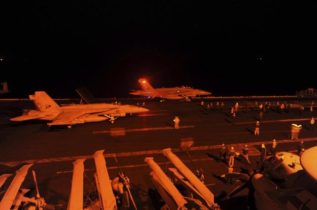 An F/A-18E Super Hornet, attached to Strike Fighter Squadron (VFA) 31, and an F/A-18F Super Hornet, attached to Strike Fighter Squadron (VFA) 213, prepare to launch from the flight deck of the aircraft carrier USS George H.W. Bush (CVN 77) to conduct strike missions against ISIL targets, in the Arabian Gulf in this U.S. Navy handout photograph provided September 23, 2014.  REUTERS/U.S. Navy/Mass Communication Specialist 3rd Class Robert Burck/Handout via Reuters