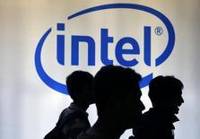 Personas caminan frente a un logo de Intel durante una exposición en Jakarta. Imagen de archivo, 05 marzo, 2014. Intel Corp dijo que pagará hasta 1.150 millones de dólares por participaciones de un 20 por ciento en dos fabricantes de chips para celulares vinculados al Gobierno chino. REUTERS/Beawiharta