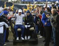 European Ryder Cup player Justin Rose and his wife Kate sit in a golf buggy as spectators applaud after his foursomes 40th Ryder Cup match at Gleneagles in Scotland September 27, 2014. REUTERS/Toby Melville