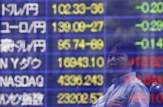 Человек изучает котировки на электронном табло в Токио 10 июня 2014 года. Азиатские фондовые рынки завершили торги понедельника разнонаправленно под влиянием валютных курсов и беспорядков в Гонконге. REUTERS/Issei Kato