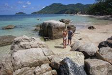 Туристы на пляже на острове Тау 19 сентября 2014 года. Министр туризма Таиланда предложила обеспечить всех приезжающих в страну туристов особыми браслетами с личными данными в попытке немного успокоить гостей азиатской страны, озабоченных убийством двух британцев на популярном курорте в Сиамском заливе. REUTERS/Chaiwat Subprasom