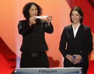 """Steffi Jones (L), head of the organization committee of the Women's World Cup holds up a slip of paper carrying the name """"Colombia"""", as she stands next to Tatjana Haenni, FIFA head of women's football competitions, during the draw in Frankfurt for the 2011 Women's World Cup, November 29, 2010. REUTERS/Alex Domanski"""