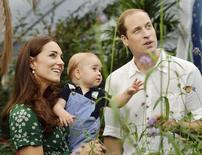 Britain's Catherine, Duchess of Cambridge, carries her son Prince George alongside her husband Prince William as they visit the Sensational Butterflies exhibition at the Natural History Museum in London, July 2, 2014. REUTERS/John Stillwell/Pool