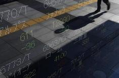 A shadow of a passerby is reflected on an electronic board displaying stock prices outside a brokerage in Tokyo October 31, 2011. REUTERS/Issei Kato