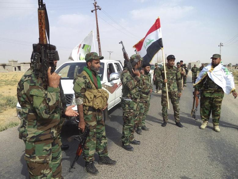 Iraqi Shi'ite militia fighters gather outside Bo Hassan village near Tikrit, northern Iraq October 2, 2014. REUTERS/Stringer