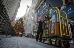 Un empleado del Hilton empuja un carro con maletas frente a la Bolsa de Nueva York. Imagen de archivo, 13 diciembre, 2013. La cadena Hilton Worldwide Holdings Inc dijo que venderá el famoso hotel Waldorf Astoria de Nueva York a la firma de seguros china Anbang Insurance Group Co Ltd por unos 1.950 millones de dólares.  REUTERS/Brendan McDermid