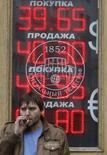 Мужчина курит у вывески пункта обмена валюты в Москве 7 октября 2014 года. Рубль во вторник утром дешевеет к доллару из-за локального дефицита валюты в условиях ограничения доступа к зарубежным ресурсам и на фоне текущих неблагоприятных тенденций глобальных рынков после снижения прогноза роста мировой экономики МВФ, в условиях укрепления валюты США и падения нефти. REUTERS/Sergei Karpukhin