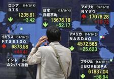 Un hombre mira una pantalla electrónica que muestra índices económicos en Tokio. Imagen de archivo, 4 septiembre, 2014. La mayoría de las bolsas de Asia cotizaba en terreno negativo el miércoles debido a las preocupaciones sobre el crecimiento global, que también empujaron los precios del petróleo a su nivel más bajo en más de dos años. REUTERS/Issei Kato