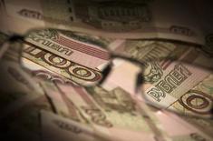 Рублевые купюры в Москве 17 февраля 2014 года. Рубль в пятницу обновляет абсолютные минимумы и границу плавающего валютного коридора ввиду дефицита валюты из-за санкций, падения нефти к многолетним минимумам и бегства от риска на мировых рынках. REUTERS/Maxim Shemetov