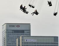 Financial offices of Canary Wharf are seen behind visitors to the O2 arena enjoying a fairground ride in east London November 23, 2011.   REUTERS/Toby Melville