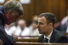 Olympic and Paralympic track star Oscar Pistorius speaks with a member of his defence team ahead of sentencing at the North Gauteng High Court in Pretoria, October 13, 2014. REUTERS/Marco Longari/Pool