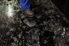 Un trabajador con botas sobre un piso cubierto de petróleo en la planta procesadora Suncor cerca de Fort McMurray. Imagen de archivo, 17 septiembre, 2014. Casi un 3 por ciento de la producción petrolera mundial es vulnerable a los recortes si los precios caen a 80 dólares por barril, haciendo no rentables algunos proyectos en Canadá, Angola, Brasil y Noruega, afirmó la Agencia Internacional de Energía. REUTERS/Todd Korol