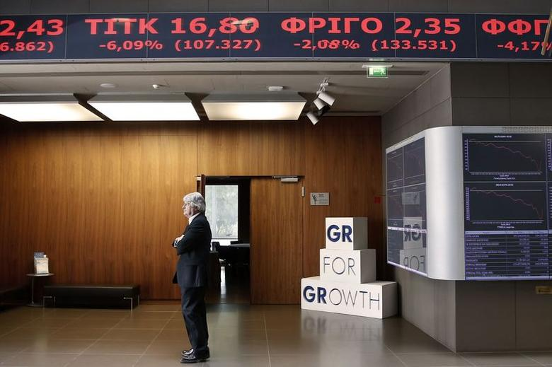 A man stands under an electronic board displaying stock prices in the reception hall of the Athens Stock Exchange in Athens October 15, 2014. REUTERS/Alkis Konstantinidis
